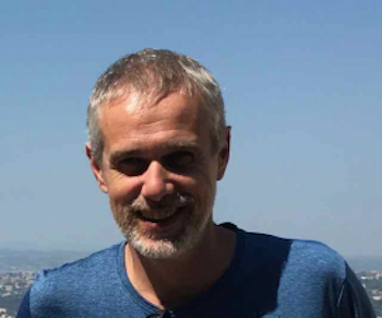 Smiling man in blue t-shirt with blue sky behind him.