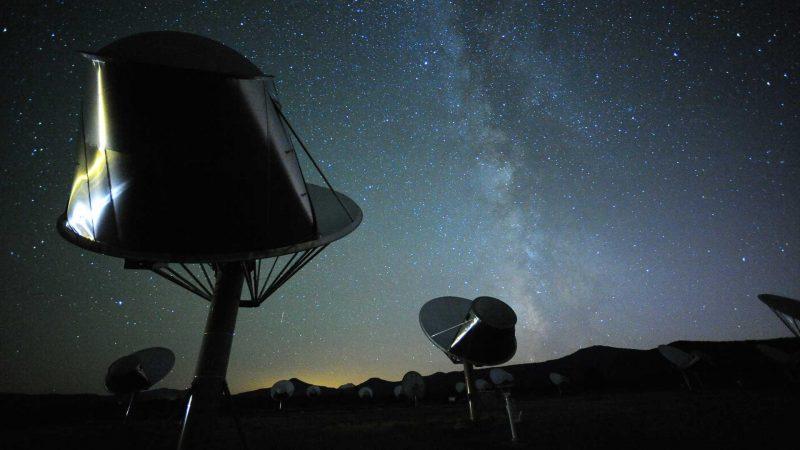 Dos antenas de radio tipo plato con la Vía Láctea al fondo.