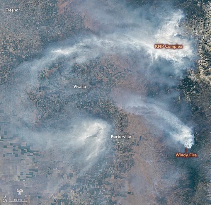 Vedere tropicală a fumului în mase albe și vârtejuri cu marcaje de orașe și incendii.
