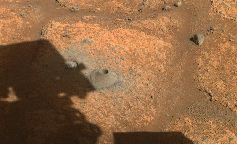 Flat reddish rock with hole drilled into it and debris around the hole.