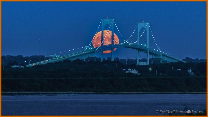 Full moon rising behind a bridge.