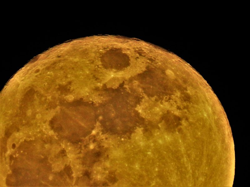 A close-up section of an orange-colored moon.