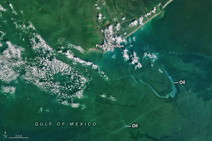 Vedere tropicală cu pământ verde și nori albi, inelul de apă urmărește petrolul adânc în marea albastru-verde.