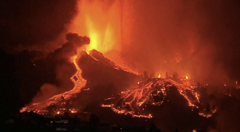 La Palma volcano: Thin streams of glowing orange lava flow down a mountainside at night.