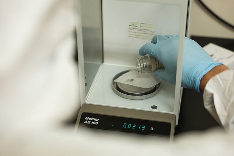 Gloved hand holding a small glass jar over a scale in a lab.