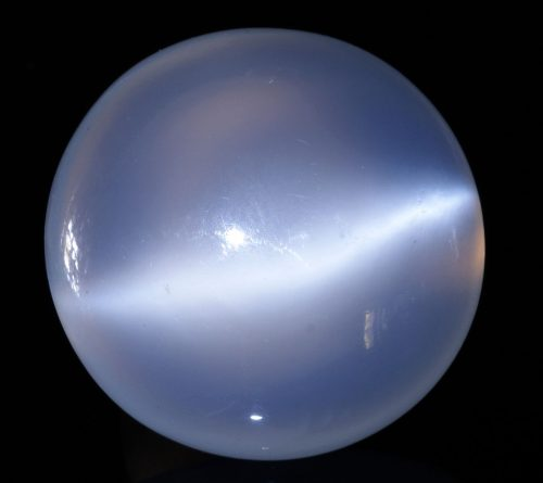 Gleaming round, smooth-surfaced stone with fuzzy line of light across it.