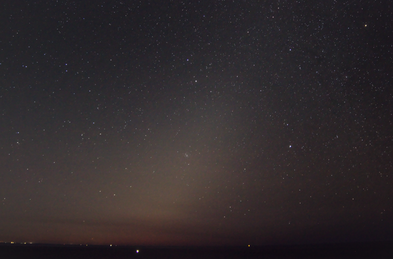 Zodiacal light or false dawn. Faint cone of light pointing to upper right in starry sky.
