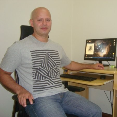 Balding man in tee shirt and jeans, sitting at a desk, with stars on computer screen.