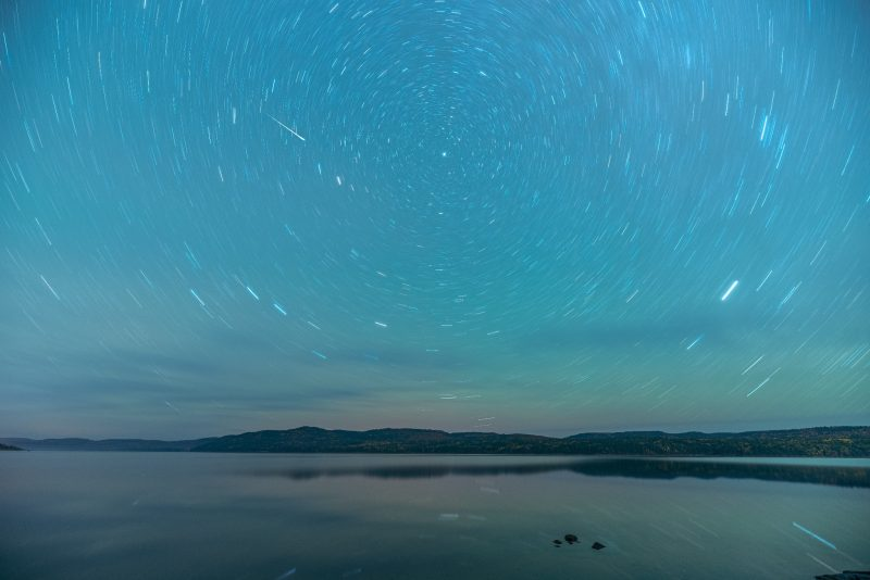 Star trails and meteor with light blue sky and water below.
