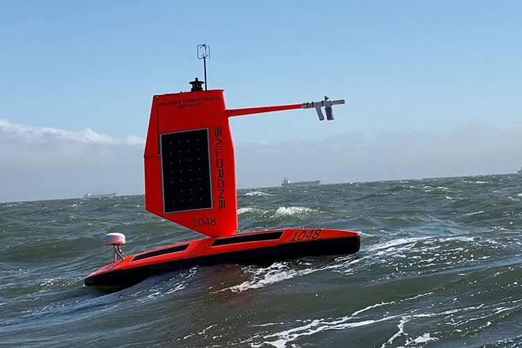 Ocean drone: Red floating craft with upright solid sail and arm with sensors.