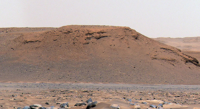 Barren, brownish rocky hill with other rocks in bare foreground.