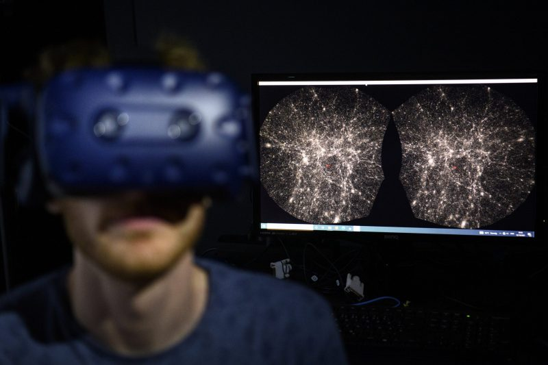 Foreground out of focus with man in VR gear, background is images of the universe.