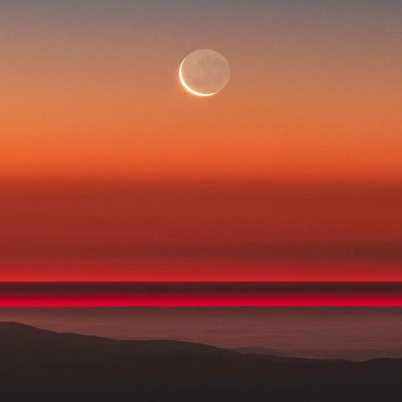 Crescent moon with earthshine, seen from a high mountain, with sunset colors.