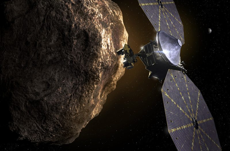 Lucy spacecraft with two large solar panels in front of large rocky object.