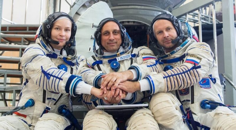1st movie in space: 3 smiling persons in astronaut attire with joined hands.